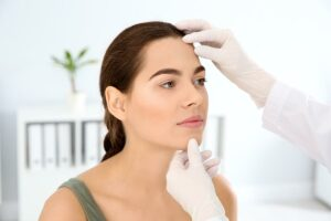 Dermatologist examining patients face in clinic Gateway ENT St Louis MO